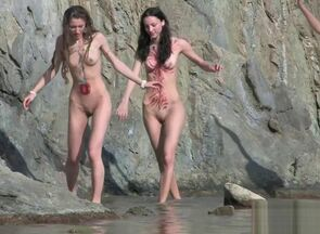 Nude young woman naturist gang out on..